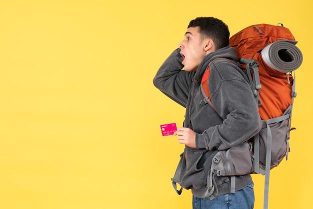Vista frontale agitato uomo viaggiatore con zaino rosso tenendo la carta sconto