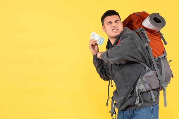 Vista frontale agitato uomo viaggiatore con zaino rosso tenendo il biglietto