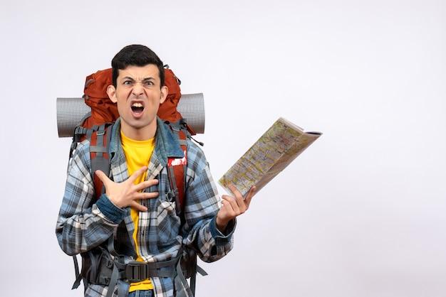 Вид спереди взволнованный молодой турист с рюкзаком, держащим карту