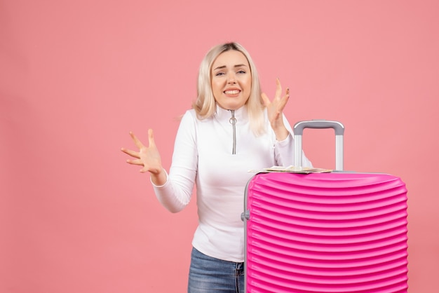 Giovane donna agitata vista frontale in piedi dietro la valigia rosa
