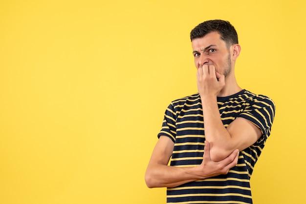 Vista frontale agitato giovane maschio in bianco e nero a strisce t-shirt sfondo giallo isolato