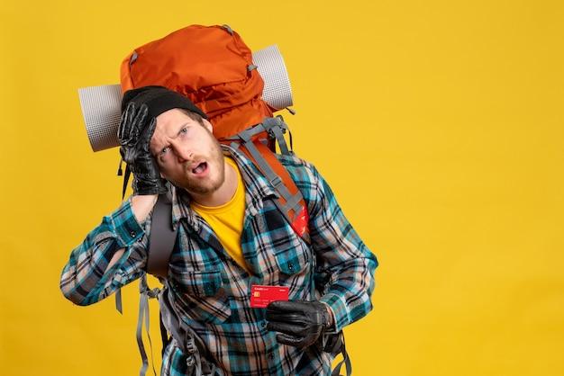 Vista frontale del giovane agitato con la carta di sconto della tenuta del viaggiatore con zaino e sacco a pelo