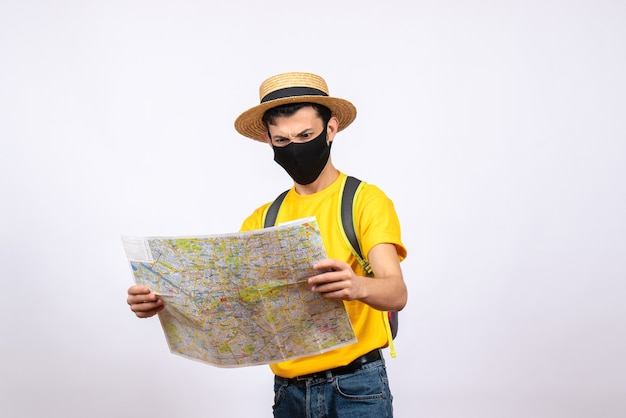 Вид спереди взволнованный молодой человек в желтой футболке и маске, смотрящий на карту