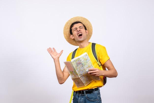 Vista frontale agitato giovane uomo con t-shirt gialla e cappello di paglia che tiene mappa