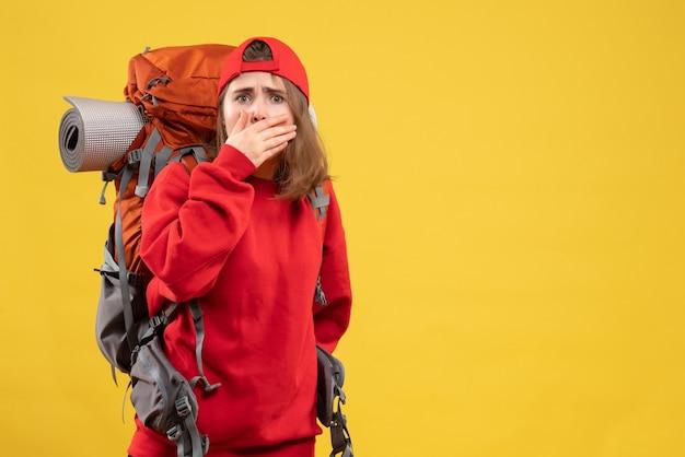 正面図黄色の壁に立っているバックパックと赤い帽子で若い観光客を興奮させた