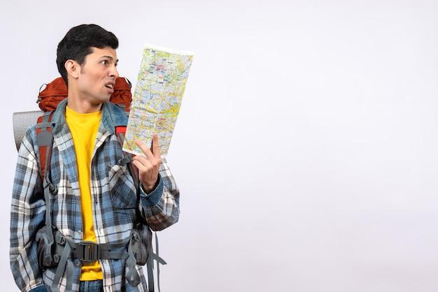 Вид спереди взволнованный молодой путешественник с рюкзаком, держащим карту