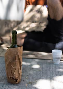 Спереди виден спирт, спрятанный в бумажный пакет и нищий