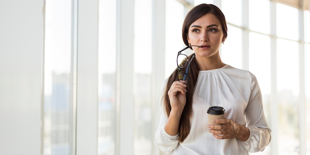 Front view of alluring businesswoman posing with glasses and coffee