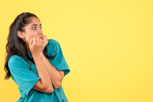 Вид спереди изумлен женщина-врач в униформе, стоя на желтом изолированном фоне