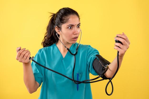Medico femminile stupito vista frontale in uniforme utilizzando sfigmomanometri in piedi su sfondo giallo