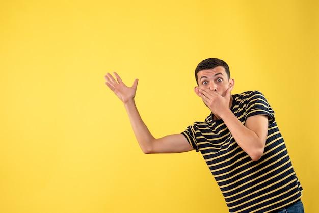正面図は黒と白の縞模様のtシャツ黄色の孤立した背景でハンサムな男を驚かせた