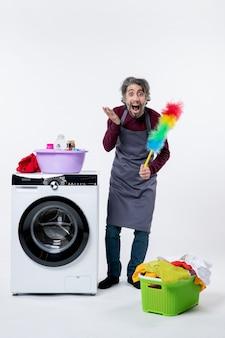 Vista frontale stupita governante uomo che tiene in mano uno spolverino in piedi vicino al cesto della biancheria della lavatrice su sfondo bianco