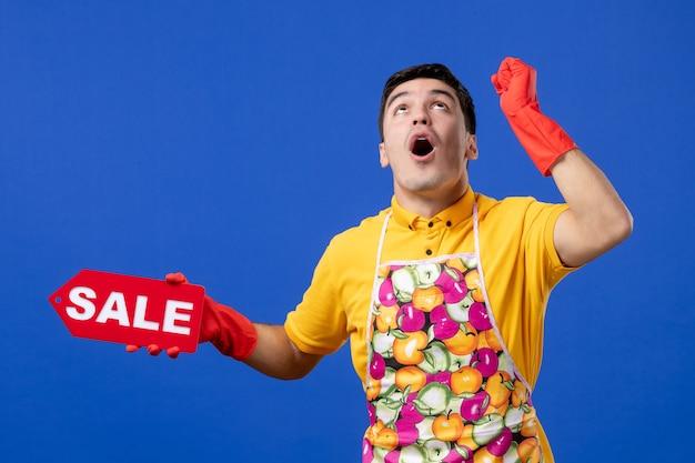 노란색 티셔츠를 입은 남성 가사도우미는 파란색 공간에 놀라움을 안고 올려다보는 판매 표지판을 들고 있는 전면 전망을 보고 놀랐습니다.