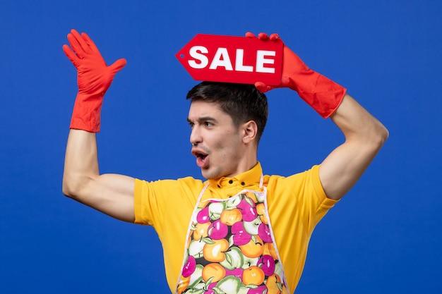 Vista frontale stupita governante maschio in maglietta gialla che alza il cartello di vendita sopra la sua testa su uno spazio blu