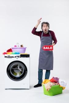 Vista frontale stupito uomo in grembiule che regge il cartello di vendita in piedi vicino al cesto della biancheria della lavatrice su sfondo bianco