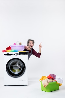 Front view amazed man in apron sitting behind washer laundry basket on white isolated background