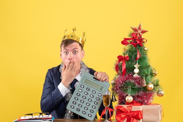 Vista frontale dell'uomo stupito che tiene la calcolatrice che si siede al tavolo vicino all'albero di natale e presenta sulla parete gialla