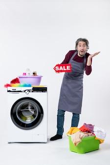 Vista frontale uomo stupito che regge il cartello di vendita in piedi vicino al cesto della biancheria della lavatrice su sfondo bianco