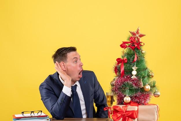 正面図は、クリスマスツリーの近くのテーブルに座って黄色の背景に提示する何かを聞いて驚いた男