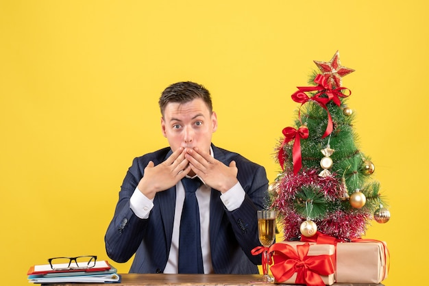 Front view amazed man putting hands to his mouth sitting at the table near xmas tree and presents on yellow background