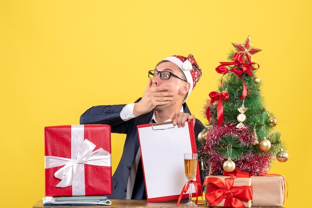 Front view amazed man sitting at the table near xmas tree and presents on yellow background free space