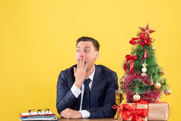 Vista frontale stupito uomo seduto al tavolo vicino albero di natale e regali su sfondo giallo spazio libero