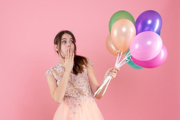 何かを見ている風船を保持しているパーティーキャップを持つ正面図驚いたパーティーの女の子