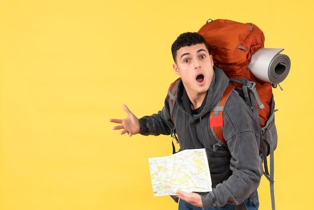 Vista frontale stupito uomo raveler con zaino rosso che tiene mappa