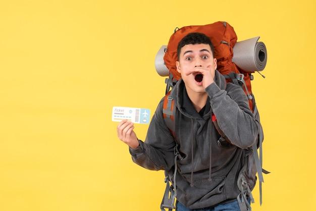 Vista frontale stupito uomo viaggiatore con zaino rosso tenendo il biglietto