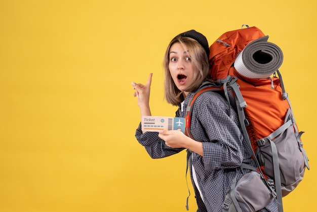 Vista frontale della donna stupita del viaggiatore con il biglietto della tenuta dello zaino che indica dietro