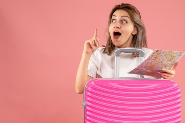 Vista frontale della ragazza stupita con la valigia rosa che tiene la mappa puntare il dito verso l'alto
