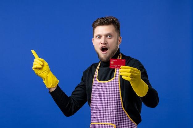 Vista frontale stupito giovane che tiene la carta nella mano sinistra sullo spazio blu