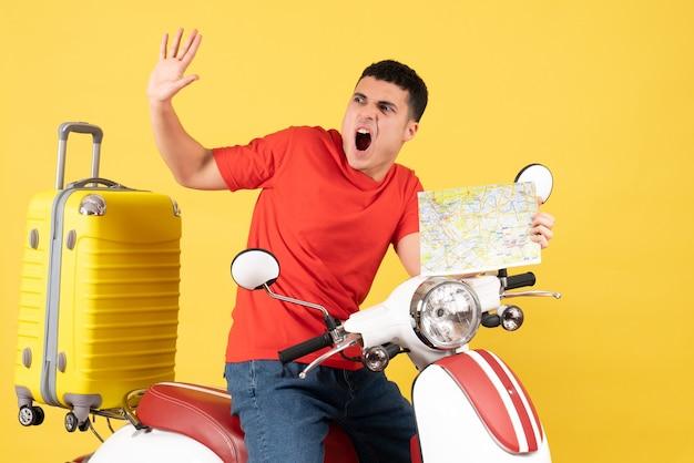 Вид спереди изумленный молодой человек в повседневной одежде на мопеде с картой путешествия Бесплатные Фотографии
