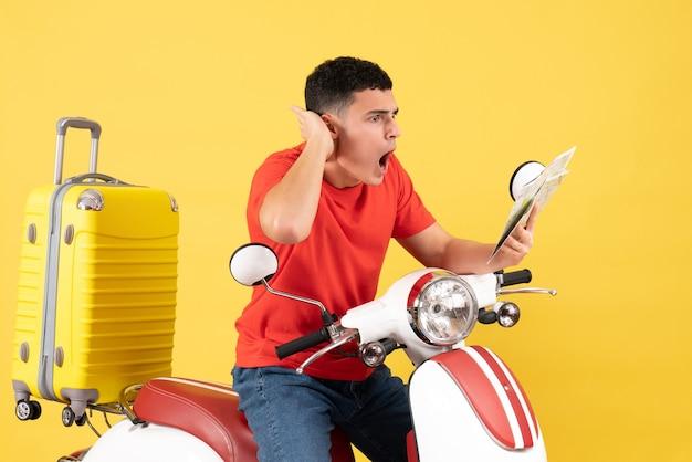 Вид спереди изумленный молодой человек на мопеде, глядя на карту на желтом