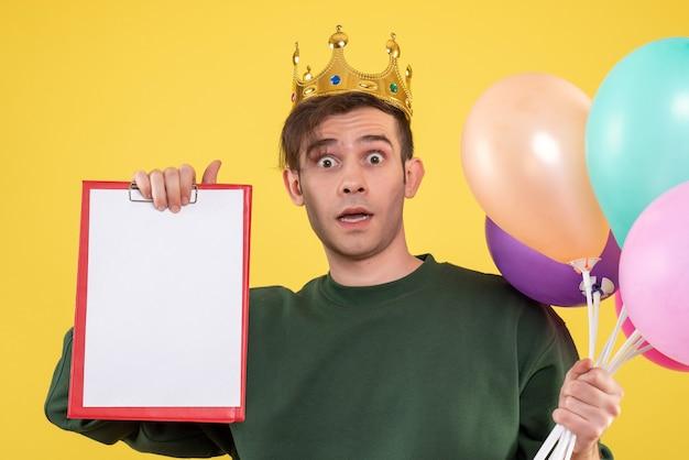Vista frontale stupito giovane uomo con corona che tiene palloncini su giallo