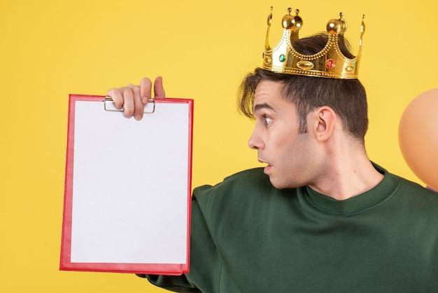 Vista frontale stupito giovane uomo con corona che tiene appunti su giallo
