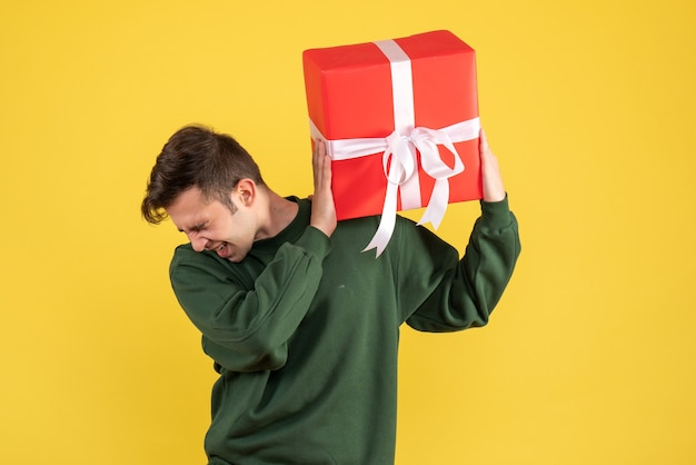 Front view amazed young man with green sweater holding gift on yellow