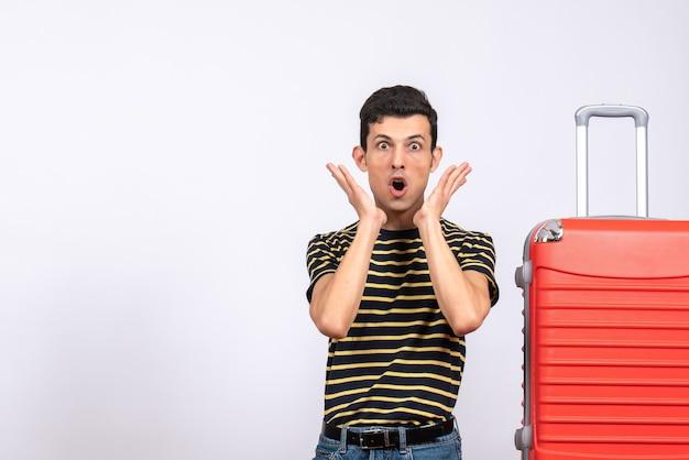 Vista frontale stupito giovane uomo con maglietta a righe e valigia