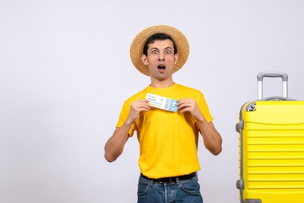 正面図は、チケットを保持している黄色のスーツケースの近くに立っている若い観光客を驚かせました