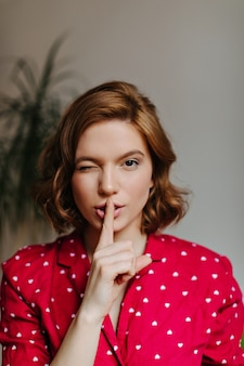 Front view of amazing woman in pajama touching lips with finger. indoor shot of carefree woman in sleepwear showing hush sign.