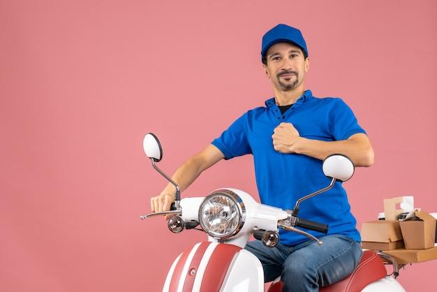 Vista frontale di un corriere ambizioso che indossa un cappello seduto su uno scooter che mostra il suo muscoloso su sfondo color pesca pastello