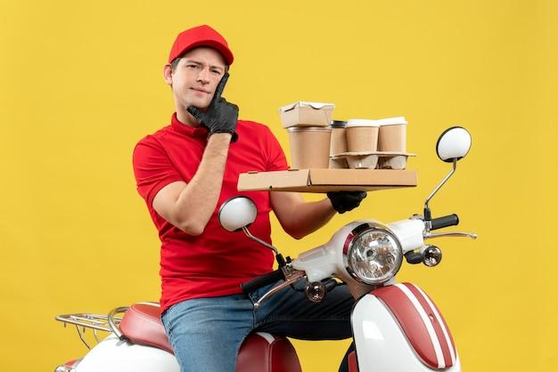 Vista frontale del corriere ambizioso uomo che indossa camicetta rossa e guanti cappello in maschera medica consegna ordine seduto su scooter tenendo gli ordini