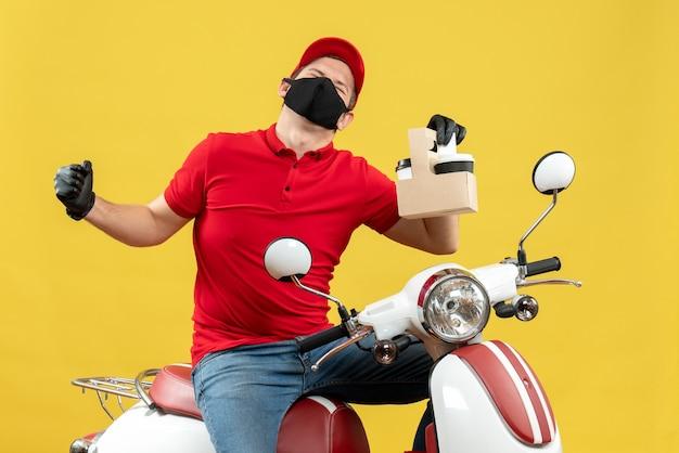 Vista frontale del corriere ambizioso uomo che indossa camicetta rossa e guanti cappello in mascherina medica seduto su uno scooter che mostra gli ordini