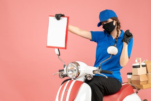 Vista frontale dell'ambiziosa donna del corriere che indossa maschera medica e guanti seduta su uno scooter con in mano fogli di carta vuoti che consegnano ordini su sfondo color pesca pastello