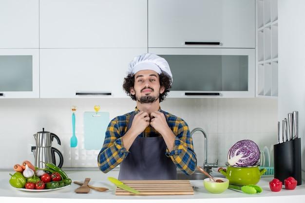 Vista frontale dell'ambizioso chef maschio con verdure fresche e cucina con utensili da cucina e nella cucina bianca