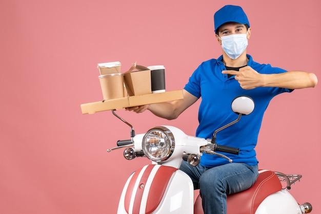 Vista frontale dell'ambizioso uomo delle consegne in maschera con cappello seduto su uno scooter che consegna ordini su sfondo color pesca pastello