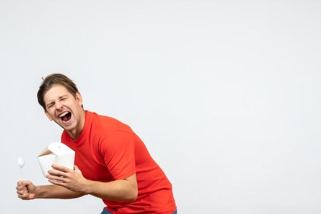 Vista frontale del giovane ragazzo ambizioso in camicetta rossa che tiene scatola di carta e cucchiaio su priorità bassa bianca