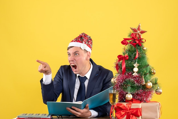 Front view angry business man yelling at someone sitting at the table near xmas tree and presents on yellow background