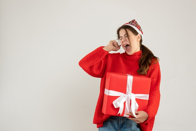 Front view angry cute girl with santa hat holding present shouting