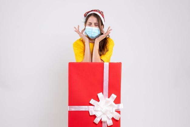 Вид спереди злая девушка в шляпе санта-клауса, закрывая уши пальцами, стоя за большим рождественским подарком
